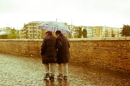 two person holding umbrella walking under the rain