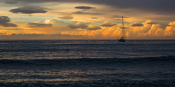 sail boat on body of water under golden hour