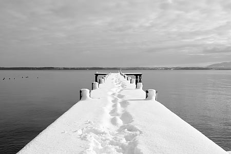 dock covered by snow under white cloudy sky