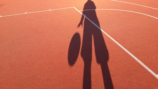 silhouette of person dribbling a ball