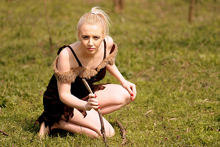 woman kneeling on one knee on grass holding stick