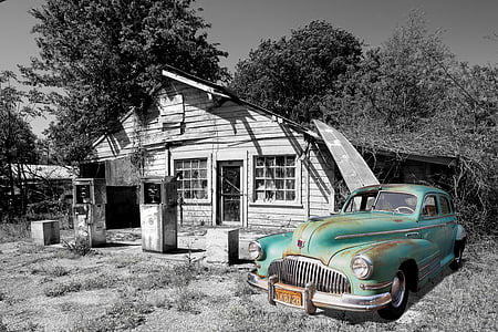 selective color photography of vintage green car parked beside white wooden house