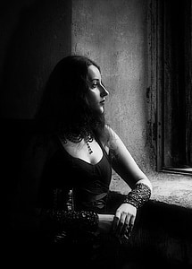 grayscale photo of woman standing beside window