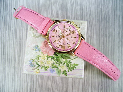 photo of round gold-colored bezel pink face chronograph watch