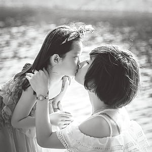 grayscale photo of woman kissing girl
