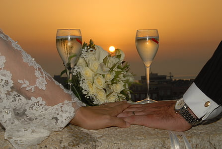 bride and groom hands on white table cloth under sunset