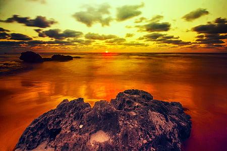 black rock formation during sunset