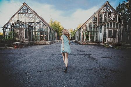 woman wearing blue dress walking through building