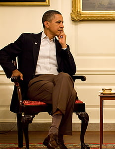 Barack Obama sitting on brown wooden armchair