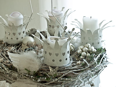 four white crown candle holders on gray nest