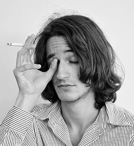 grayscale portrait photo of man holding a cigarette