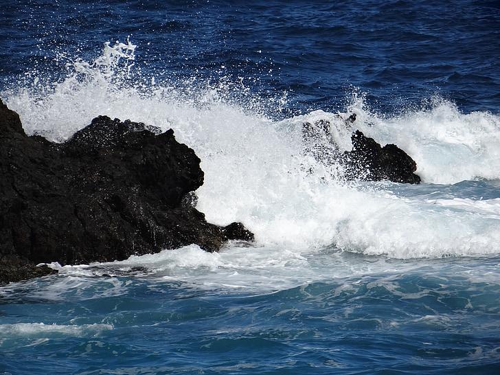 high waves crashing rock formation at daytime