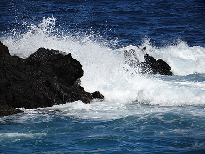 high waves crashing rock formation at daytime