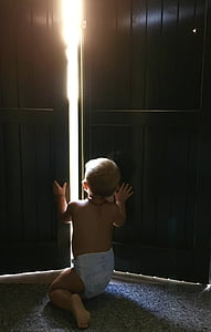 baby kneeling on the ground trying to open the door