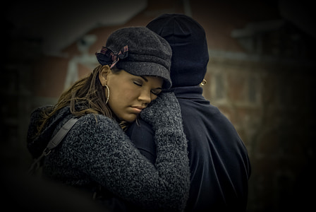woman hugging person in black hat