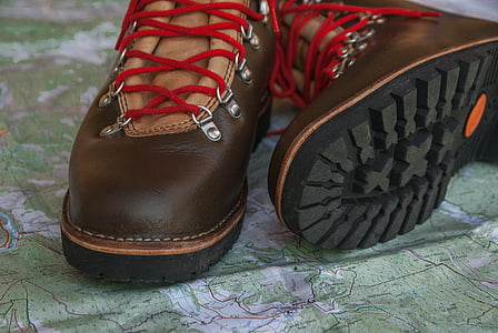 brown-and-black leather work boots on green textile