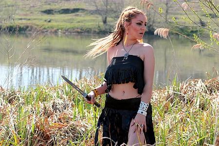 woman wearing black skirt holding gray steel sword