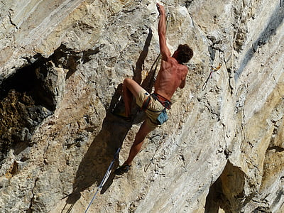 man climbing mountain during daytime