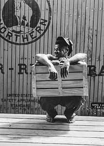 man crouching while holding wooden crate