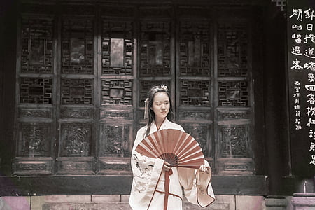woman wearing white dress holding red fan near black wall