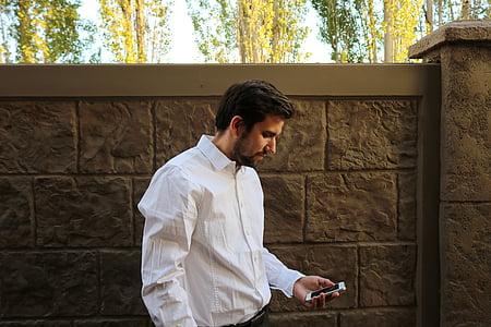 man wearing white dress shirt while holding phone