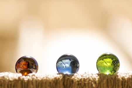 selective focus photography of three assorted-color marbles on brown surface