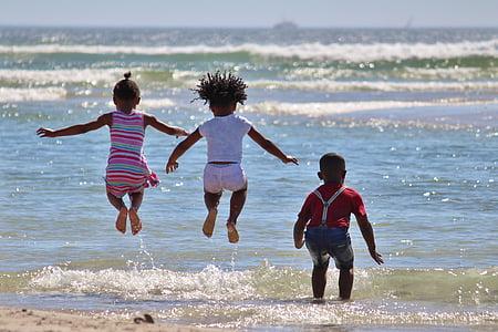 three children playing on seashore during daytime
