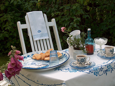 biscuits on top of round white and blue toile ceramic plate on top of white and blue floral table cloth near white wooden Windsor chair on garden during daytime