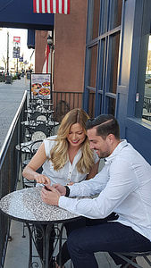 man and woman sitting on bistro chairs
