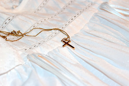 gold-colored cross pendant necklace on white textile \