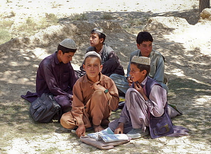 five boys sitting on gray surface during daytime