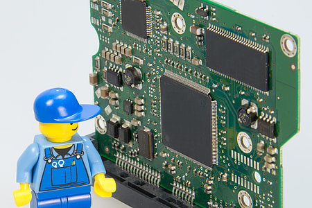 photo of blue LEGO character action figure looking at circuit board