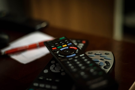 shallow focus photography of black remote controls