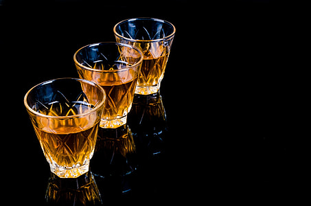 three clear shot glasses on black surface