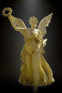 angel wearing one-shoulder dress statue
