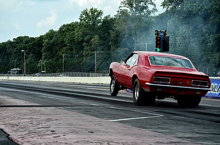 red muscle car on drag strip during daytime