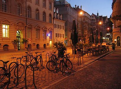 gray bicycles park near green patio umbrella during nighttime