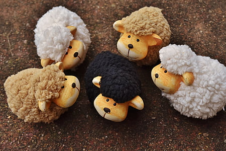 five brown, white, and black sheep plush toys