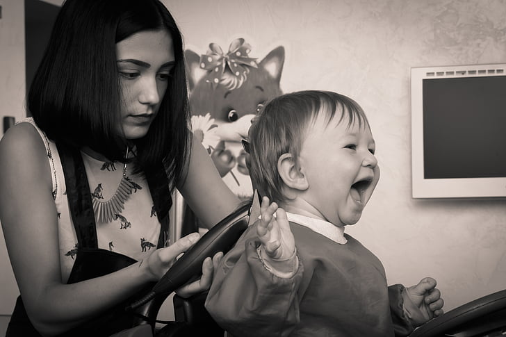 grayscale photography of girl doing hair cut on child