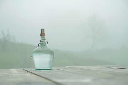 clear glass bottle on gray wooden table