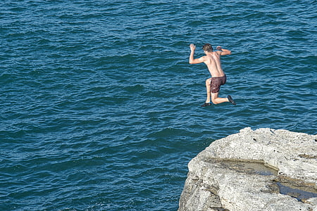 photo of man that jumps on cliff near body of water
