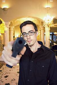 man wearing black dress shirt pointing gun forward