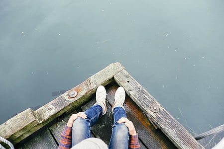 top view photo of person in denim pants sitting on brown wooden dock over body of water