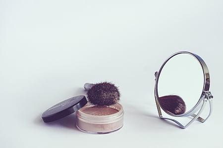 makeup brush beside vanity mirror