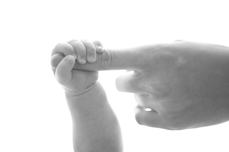 toddler and parent holding finger in greyscale photography
