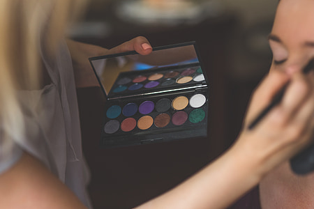 woman in white top holding make-up palette