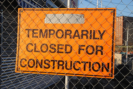 orange signage in front of fence