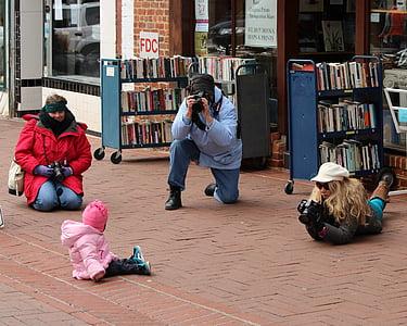toddler sitting on brown pavement
