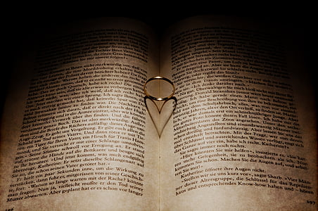 silver-colored ring between book forming heart shadow