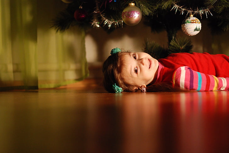 girl lying on the floor under Christmas tree